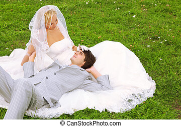 Head of young groom lies on the knees of beautiful bride wearing white dress play on green field