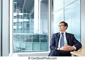 Businessman wearing glasses on the background of a large window in the office