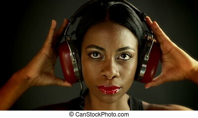 head shot close up of a sexy young woman listening to music on headphones
