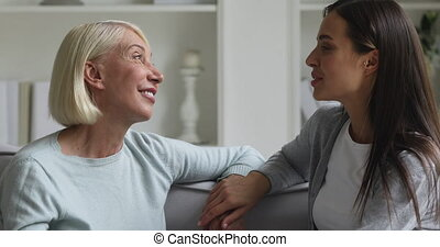 Head shot close up side view smiling middle aged woman relaxing on couch with happy grown up daughter, talking about life moments. Bonding affectionate two generations family chatting in living room.