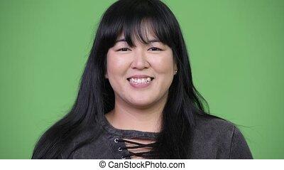 Head shot of beautiful overweight Asian woman smiling -...