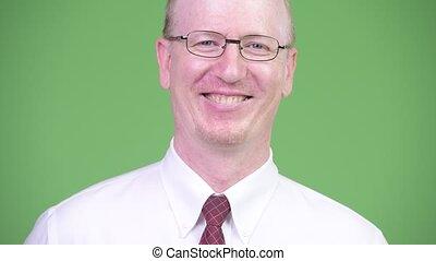Head shot of happy mature bald businessman wearing...