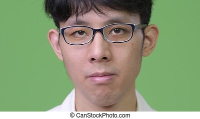 Head shot of young Asian businessman against green...