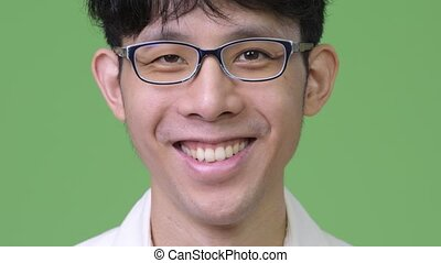 Head shot of young Asian businessman smiling - Studio shot...