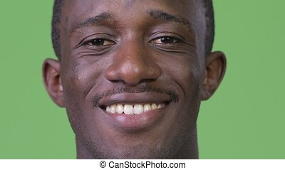 Head shot of young happy African man smiling - Studio shot...