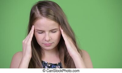 Head shot of young stressed woman having headache