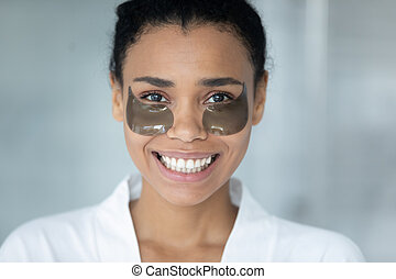 Head shot portrait African American woman with under eye mask