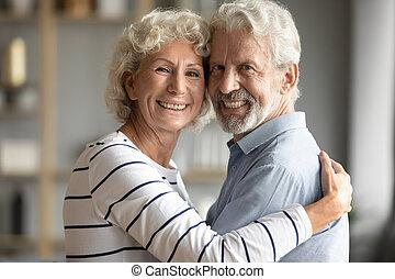Head shot portrait happy older couple hugging, looking at ...