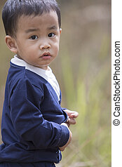 head shot portrait of asian little boy looking eyes contact to camera