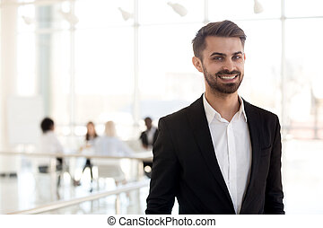 Head shot portrait of successful businessman standing in company office hallway, excited happy male employee posing for photo, looking at camera, smiling worker making picture at workplace