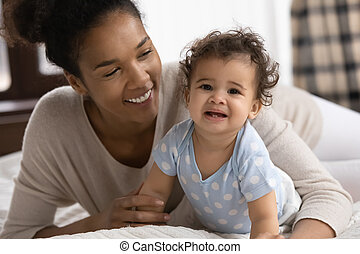 Head shot portrait smiling African American mother and toddler girl
