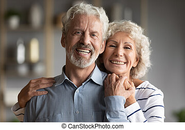 Head shot portrait smiling older man and woman hugging, ...