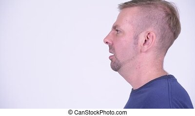 Head shot profile view of angry blonde man screaming -...