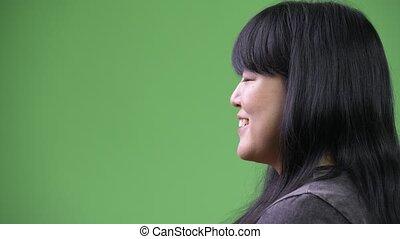 Head shot profile view of beautiful overweight Asian woman...