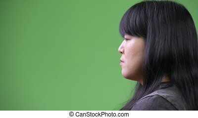 Head shot profile view of beautiful overweight Asian woman -...