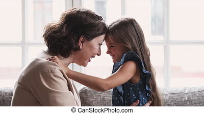 Affectionate older retired grandmother touching foreheads with little granddaughter.