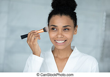 Head shot smiling African American woman applying daily makeup