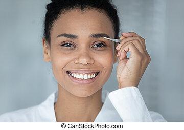 Head shot smiling African American woman plucking eyebrows with tweezers
