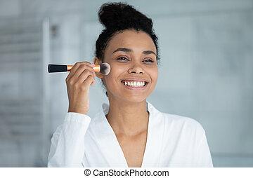 Head shot smiling African American woman using cosmetics brush
