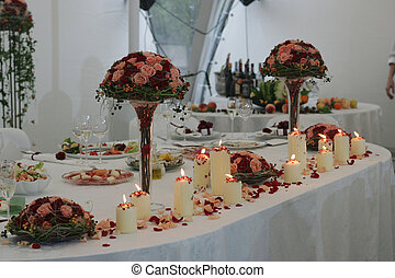 Close up of flowers and candles on head table at wedding reception.