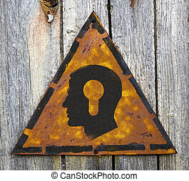 Head with a Keyhole Icon on Rusty Warning Sign.