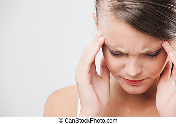Headache - An attractive young woman with her eyes closed is...