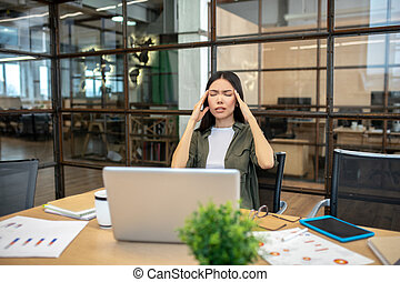 Long-haired brunette asian girl suffering from headache