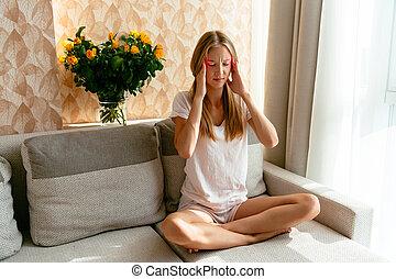 Headache of woman sitting on sofa at home