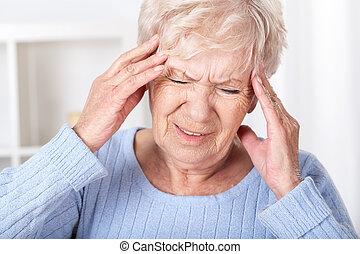 Headache - Senior woman suffering from headache