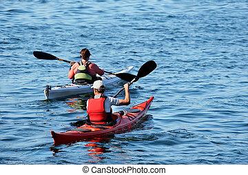 Heading out - two kayacs on a calm blue lake