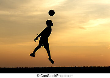 Heading the soccer ball at sunset.