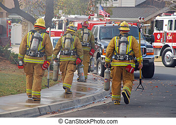 Fire fighters heading to a burning house.