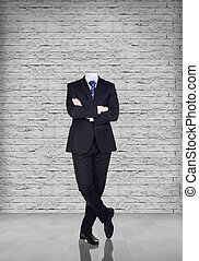 Headless businessman stand on gray brick background