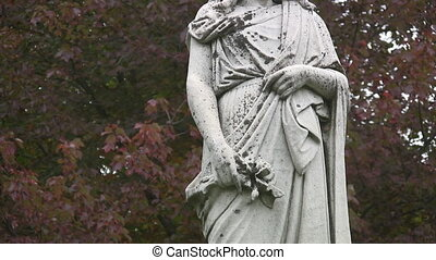 Headless cemetery statue. - An antique statue in a cemetery....