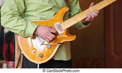 headless musician plays electric guitar