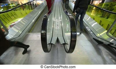 headless people rushing dows and up on escalators in mall