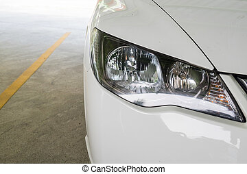 Headlight of a white modern car at parking lot