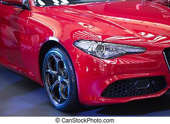 Headlight of modern car - Close up of headlight on shiny red...