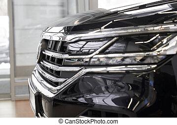 Headlight of new black auto in dealership showroom.