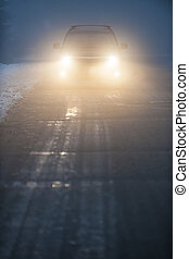 Headlights of car driving in fog - Bright headlights of a...