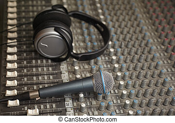 headphones and microphone on old dirty sound mixer pult. microphone in focus