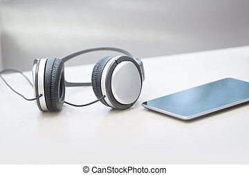 Headphones and tablet computer on a table