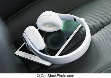 Headphones and tablet computer on the car seat