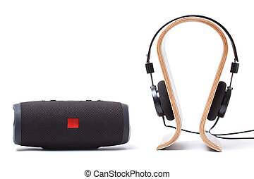 headphones in black and wireless portable speaker system on a white background