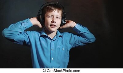 headphones little boy listens to music studio on black...