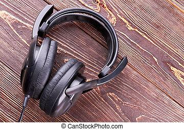 Headphones on brown textured wood.