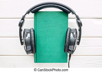 Headphones on the book in hardcover