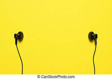 Headphones on yellow background with text space