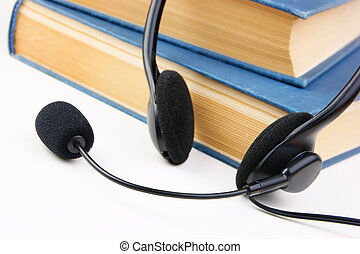 Headphones with a microphone and a stack of books