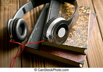 headphones with books on wooden table